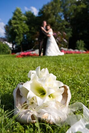The brides bouquet with her shoes in foreground on a meadow. Bridal couple defocused in background. Blue sky, it is summer! Stock Photo - 1613718