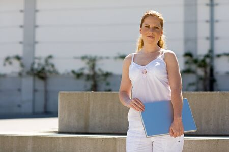 airy: Woman with a laptop in her arms. Airy white casual wear. Outdoor.