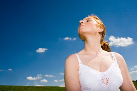 Woman with closed eyes. Head towards the sun. Recreation, smelling the fresh air. Blue sky with white clouds as background. And some grass.