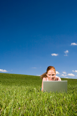 Young adult woman lying on the green grass going to the horizon. With silver Laptop. Above blue sky with clouds.