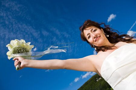 arm bouquet: Fancy Perspective. Bride holds her bridal bouquet on outstretched arm. Deepblue sky as background. Sunny weather. Adult bride.