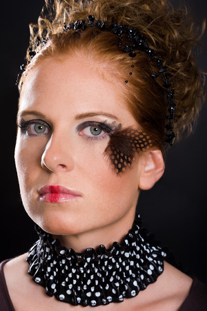 voguish: Attractive woman, unusual rogued, with feather on one eye and black-white vogue toby collar. Dark background.