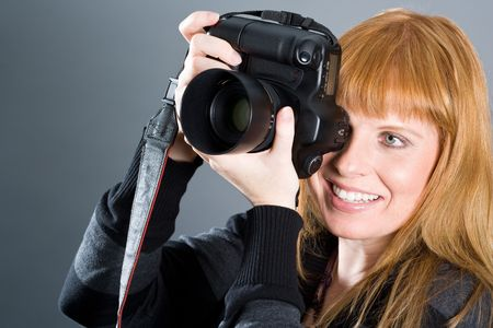 Nice woman taking pictures with professional camera.