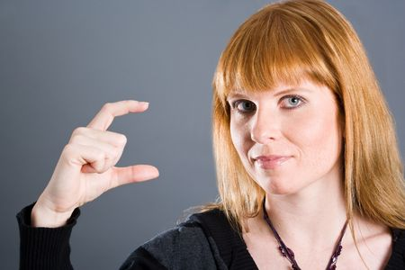 cynical: Woman showing a small gap or small thing with her fingers. Stock Photo