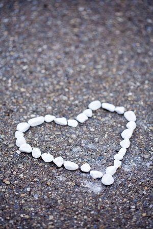 White stones on asphalt. Heartshaped. Imagens