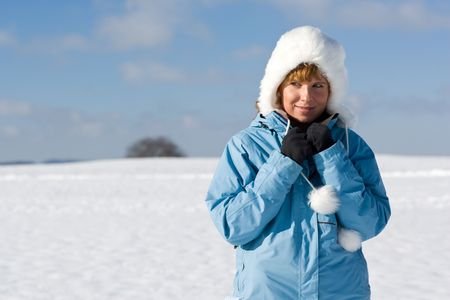 snowlandscape: Nice woman in winter-landscape, looking to the left to the copyspace.