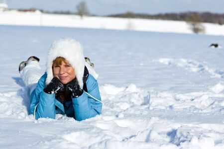 snowlandscape: Young woman is lying in the snow and looking to you.