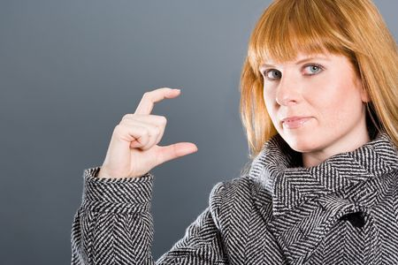 sceptic: Woman with coat showing a small gap or small thing with her fingers.