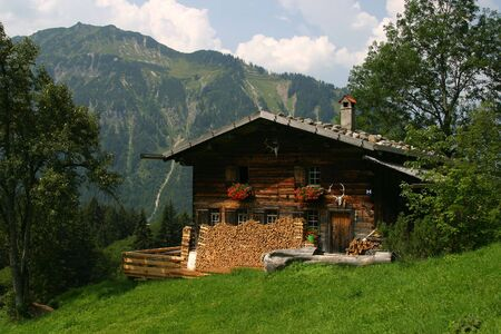German wooden house within the mountains. Green grass.  Imagens