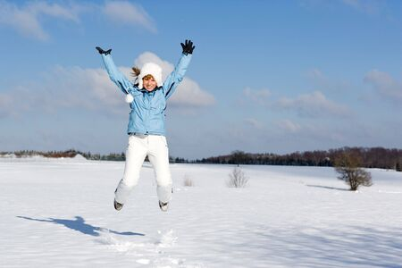 snowlandscape: Woman jumping happily outdoor in the snow