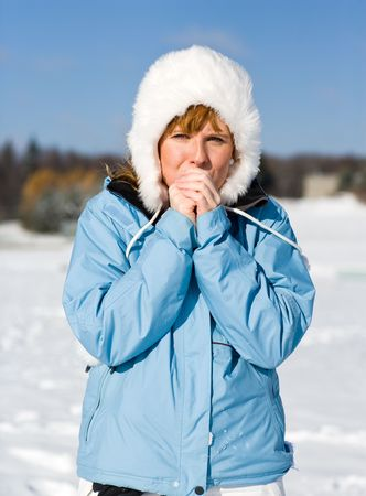 wintersport: Woman breezing warm air into her cold fingers in winterclothes Stock Photo