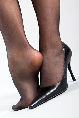 Two female feet in black pantyhose and one black shoe