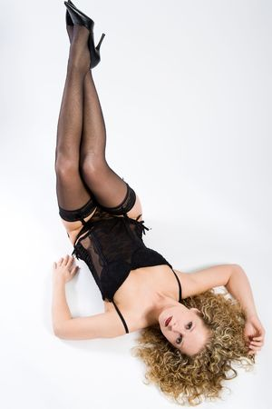 Woman in black lingerie is lying down on her back, lifting her legs and looking to you Stock Photo - 2363017