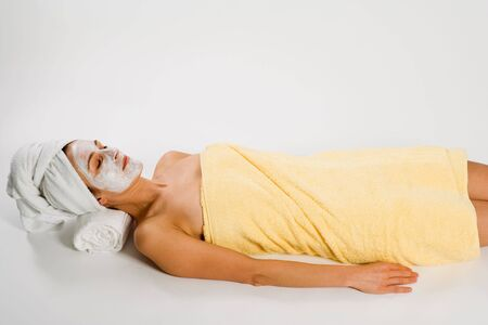 Woman in towels and facemask lying on white background. photo