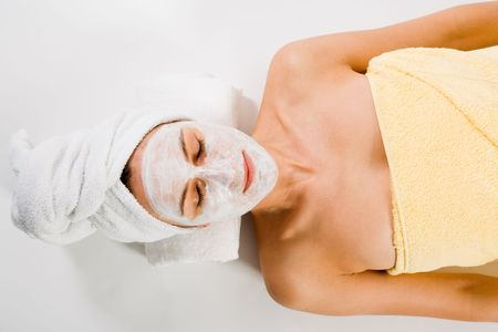 facemask: Woman with closed eyes and facemask and towels on white. Stock Photo