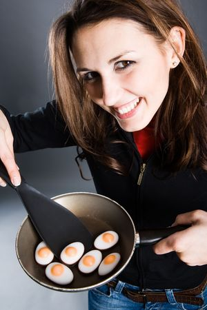 Woman with small pan in her hand. In pan are small eggs made out of sugar. Funny!