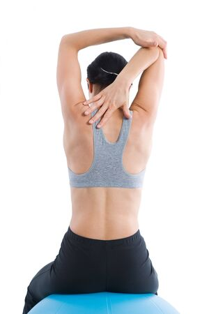 Sporty woman from behind, stretching her right arm