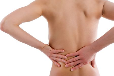 Naked womans body from behind - she holds her lower back