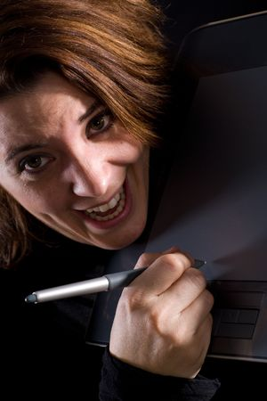 manic: Dramatic light and manic woman holding a graphics tablet.