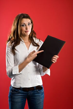 Doubting woman pointing to a black folder. photo