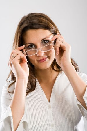 attaching: Attractive woman attaching eyeglasses while viewing at you with a slight smile.