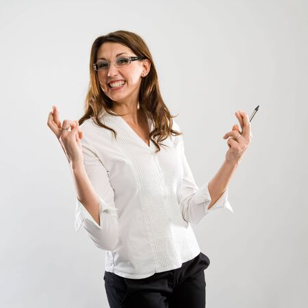 hurray: Woman with fingers crossed and a big grin - she hopes to win. Funny pose! Stock Photo