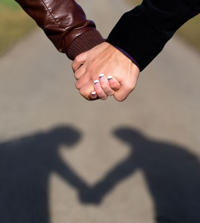 Shadow of couple heartshaped. Two hands holding each other outdoor. Focus on hands, blurred way. Stock Photo