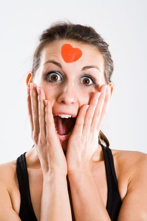 forgotten: Attractive woman with red heartshaped plaster on forehead. Seems to be totally surprised