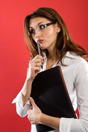 Attractive woman with glasses and Folder, holding a pen to her mouth while posing thoughtfully. photo