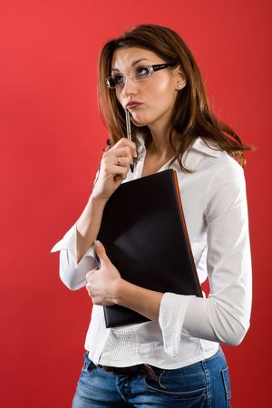 Standing attractive woman with glasses and Folder, holding a pen to her mouth while posing thoughtfully. photo