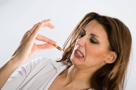 nauseous: Woman grimacing while holding a little cracker with her fingertips.