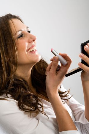 primp: Appealing nice woman while making uo with lipstick and little mirror.