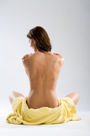 Beautiful sitting naked woman from rear view with towel around hips on white background. Stock Photo