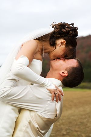 Groom lifted his bride - they are kissing each other with a smile.