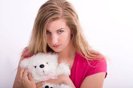 angry teddy: Young woman hugs her teddy bear while looking offended or angry.