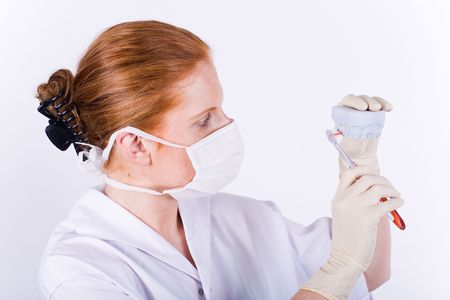 Female dentist showing how to clean your teeth with a mould. 2 photo