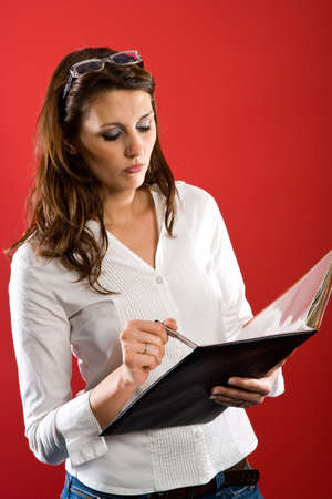 Attractive woman holding folder while tapping wth a pen on a page.
