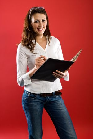 Nice woman smiling to you while holding a black folder in her hand.