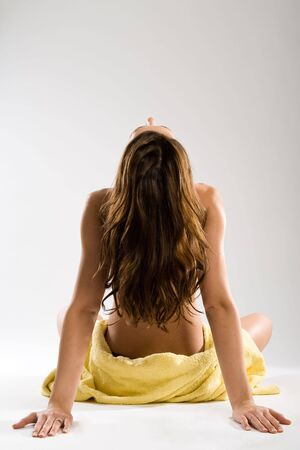lean back: To throw ones head back. Attractive sitting woman from behind with towel around hips. Stock Photo