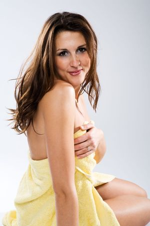 Attractive sitting woman holding enwrapped towel and looking to you.