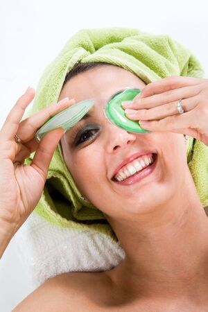 Woman with Towel around head lifting on of the Eye-Pads and smiling nice to you. Imagens
