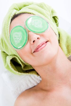 Woman with Towel around head relaxing with Eye-Pads, smiling with closed mouth. Face and shoulder.