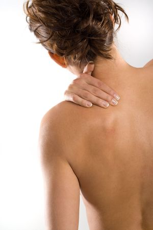 Woman from behind, naked body, holding her neck on the left side. Vertical. Stock Photo