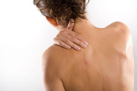 Woman from behind, naked body, holding her neck on the left side.
