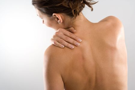 Woman from behind, naked body, holding her neck on the left side. Face to the left. Body tensed.