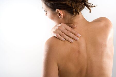 Woman from behind, naked body, holding her neck on the left side.  Imagens