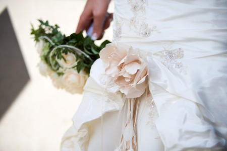 Beautiful wedding dress detail. Hand holding bouquet in background photo