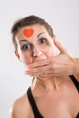 Woman with surprised look holding hand over her mouth and wearing a heart on her forehead. photo