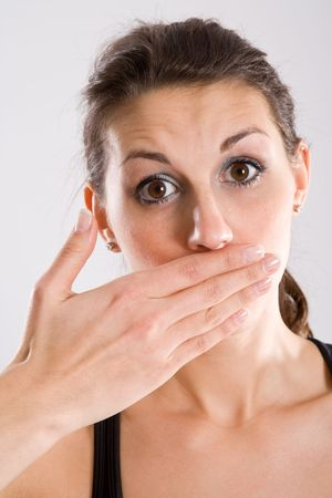 Portrait of woman with hand over mouth and surprised expression. photo