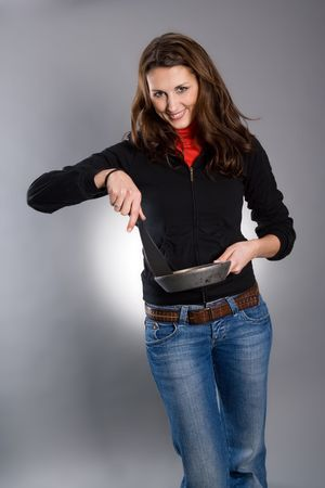 A pretty young woman in jeans, holding a small cooking pan and spatula. Gray studio background photo